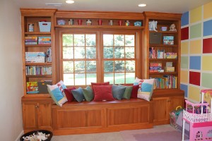 Built toy and book storage around a basement window. Window seat has more storage.